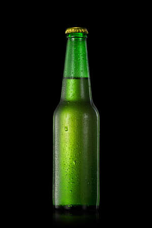 green beer: Green beer bottle with water drops isolated on black Stock Photo