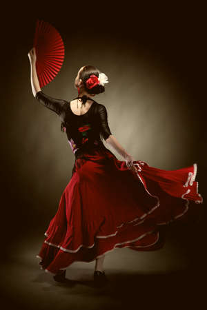 young woman dancing flamenco on black