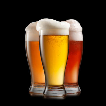 Different beer in glasses isolated on black background photo