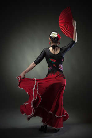 young woman dancing flamenco with fan on black photo