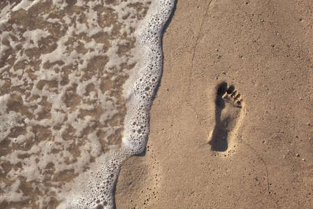 sand with footprint and water wave photo