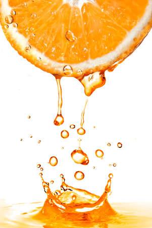 orange slice and splash of juice isolated on white photo
