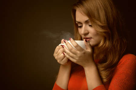 woman holding hot cup and smiles photo