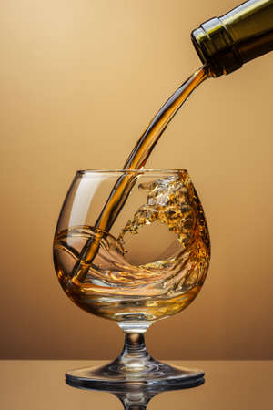 Cognac pouring from bottle into glass with splash on brown background photo