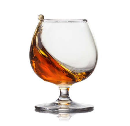 amaretto: Splash of cognac in glass isolated on white background