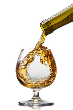 Cognac pouring into glass with splash isolated on white background photo