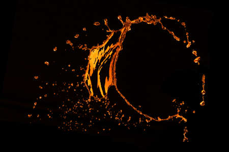 orange water splash isolated on black photo