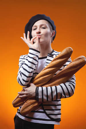 woman holding baguettes and shows that taste is delicious photo