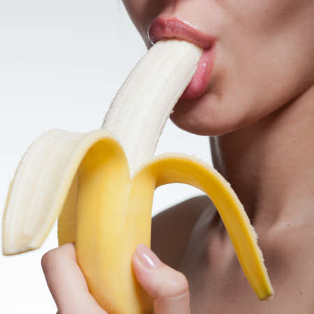 sexy food: Young woman biting banana isolated on white