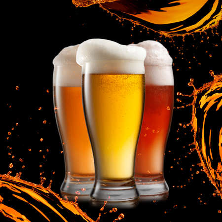 Different beer in glasses wish splash isolated on black background Stock Photo