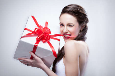 Young smiling woman holding gift photo