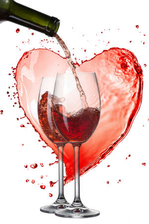 Red wine pouring into glasses with splash against heart isolated on white photo