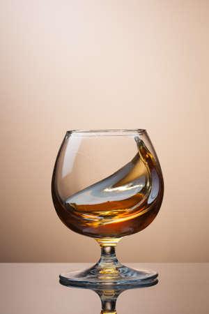 amaretto: Splash of cognac in glass on brown background