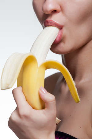 donna sexy: Giovane donna mordere banane isolato su bianco