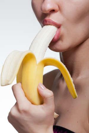 La mujer joven morder plátano aislado en blanco Foto de archivo