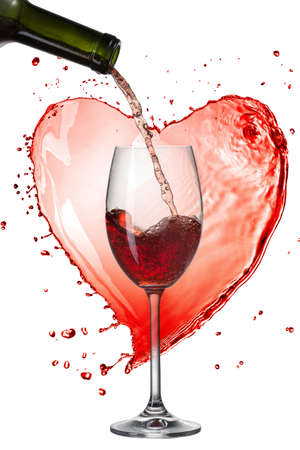 Red wine pouring into glass with splash against heart isolated on white photo