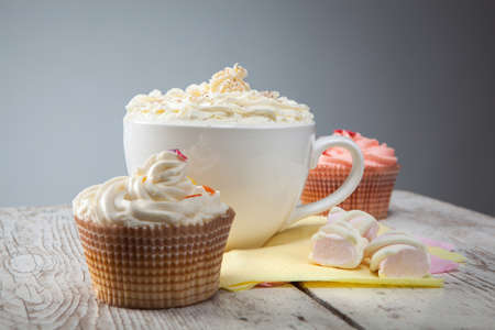 hot chocolate with marshmallows, cream and cupcakes on wooden background photo