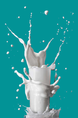 tourquoise: milk splash in glass isolated on blue background