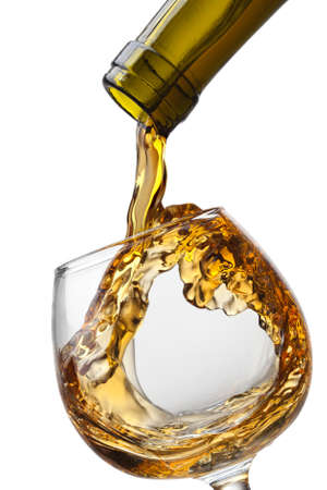 white wine glass: Cognac pouring into glass with splash isolated on white background