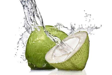 splash van water op groene kokosnoot geïsoleerd op wit