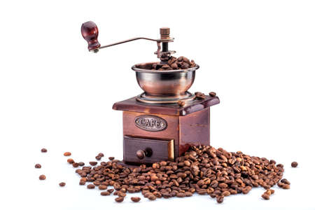 grinder: Retro manual coffee mill on roasted coffee beans isolated