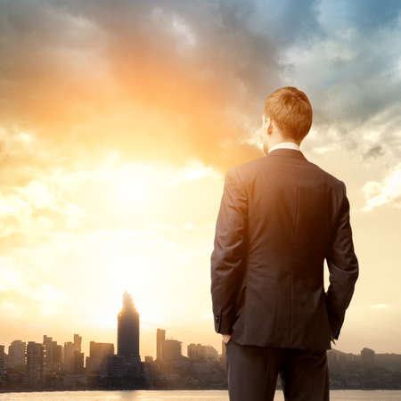 business man look sunrise in the city photo