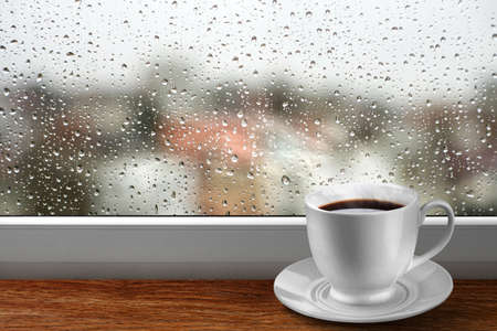 Coffee cup against window with rainy day view photo