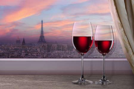 Uitzicht over Parijs en de Eiffeltoren op zonsondergang van venster met twee glazen wijn