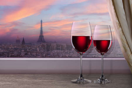 View of Paris and Eiffel tower on sunset from window with two glasses of wine photo