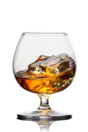 amaretto: Splash of whiskey with ice in glass isolated on white background