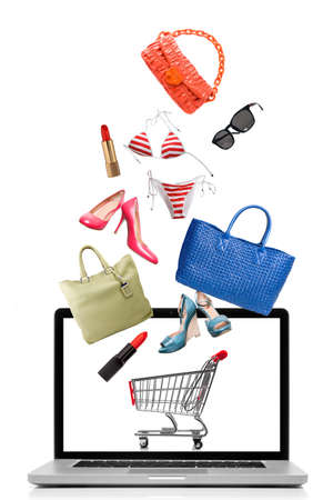 Things to buy falling into notebook isolated on white. Shopping concept photo