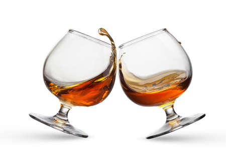 amaretto: Splash of cognac in two glasses isolated on white background Stock Photo