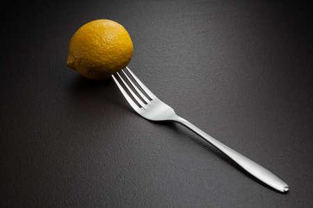 lemon and fork on black