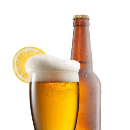 Beer in glass with lemon and bottle isolated on white photo