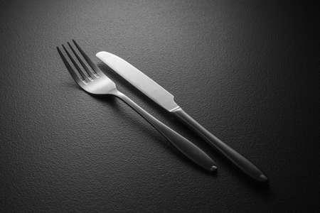 knife and fork on black