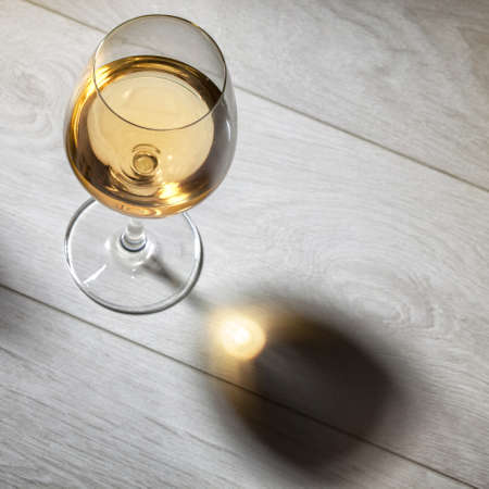 glass of white wine: Glass of white wine on wooden table. Top view