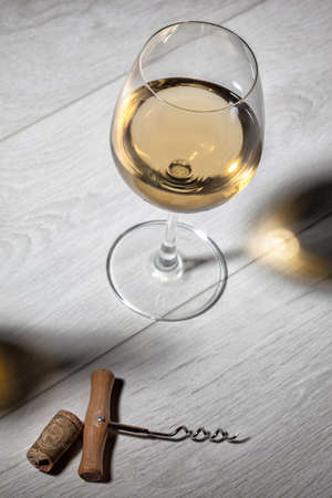 wooden table top view: Glass of white wine on wooden table. Top view