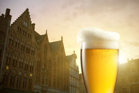 Glass of beer against silhouettes of houses in Bruges, Belgium photo