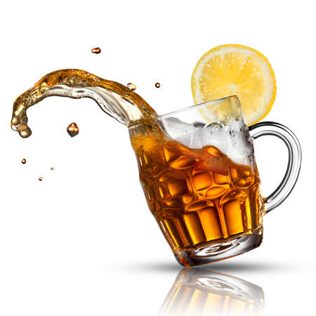 Beer splash in glass with lemon isolated on white photo