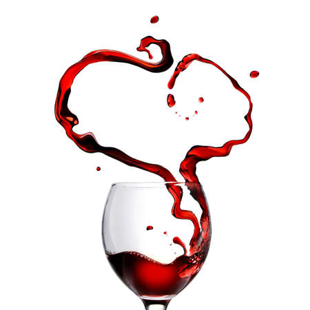 Heart made of pouring red wine in glass isolated on white photo