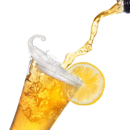 single beer bottle: Beer pouring from bottle into glass with lemon isolated on white
