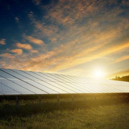 paneles solares: paneles solares bajo el cielo azul en la puesta del sol Foto de archivo