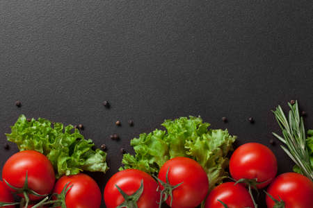 red tomatoes with green salad on black photo
