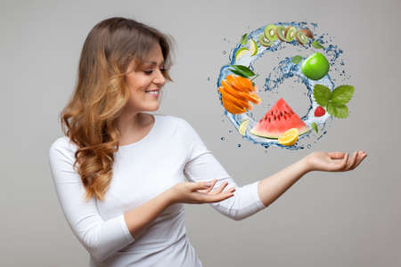 smiling woman with fruits and water splash on grey background photo