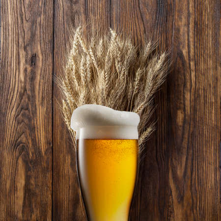 wheat beer: Glass of beer with wheat on wooden background Stock Photo