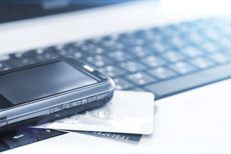 Credit cards and mobile phone on the notebook Stock Photo - 29495344