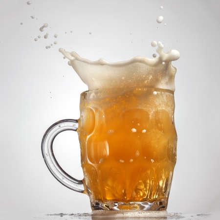 vasos de cerveza: Splash Cerveza en vidrio aislado sobre fondo blanco Foto de archivo