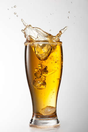 Ice falling into beer glass with splash isolated on white background photo