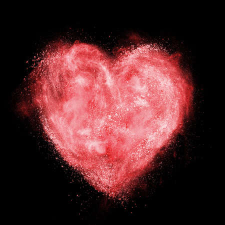 red heart made of white powder explosion isolated on black background