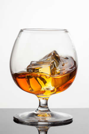 postproduction: Splash of whiskey with ice in glass isolated on white background. Raw image, no postproduction